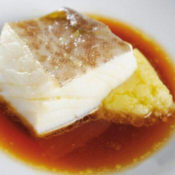 Bacalao con puré de patatas y nueces sobre caldo de espinas tostadas