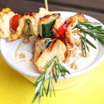 Brochetas de pollo de corral con pimientos de colores y crema de nueces