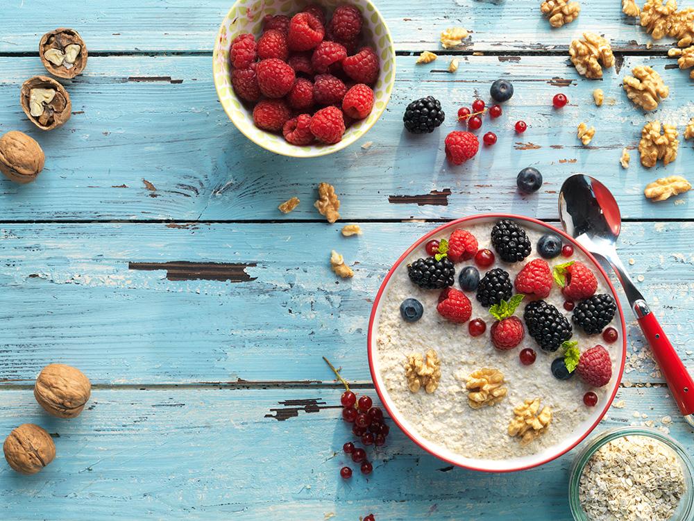 Porridge de leche de nueces y avena con topping de frambuesas, moras y miel