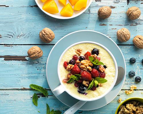 Crema de yogur, queso y melocotón con topping  de frutos rojos y nueces